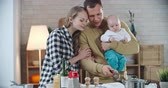 жена : Father holding little baby and making coffee for his wife in the kitchen then giving her cup and she smelling it