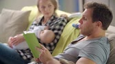 prole : Father reading aloud fairytale to his wife and newborn son on her hands