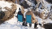escandinávia : Rear view of Nordic couple sitting on camping chairs at snowy mountain edgeand talking Vídeos