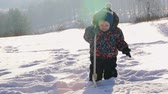 снежный : Adorable baby boy in warm clothing standing in snow and playing with wooden toy spade on sunny winter day