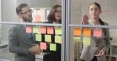 lembrete : Group of young Asian business people standing behind office glass wall,creating ideas for business growth and writing the, down on sticky notes