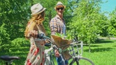 randka : Tracking shot of young couple in straw hats walking with their bicycles through green summer park and chatting,flower bouquetlying in bike basket
