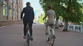 cyklus : Rear view tilt upof Asian business people in suits riding bicycles down city street
