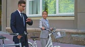 cyklus : Medium tracking shot ofCaucasian businessman explaining something to Asian businesswoman as they walk with bicycles down city street