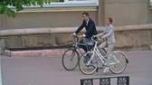 cyklus : Tracking shot ofyoung Asian businesswoman and Caucasian businessmanriding bicycles down streetand talking