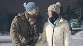 снегопад : Tilt up of carefree young couple ice-skating and kissing at outdoor rink in park under falling snow