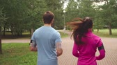 practice : Rear view of young couple jogging through park together