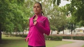 físico : Pretty girl in bright pink training jacket listening to music with earphones while running in park