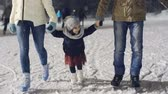 snowfall : Adorable little girl enjoying ice skating with her parents at outdoor rink in park Stock Footage