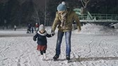 снегопад : Positive young man teaching his lovely little daughter to ice skate at outdoor skating rink