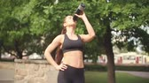 relaxation : Panning shot of attractive fit girl in black sports bra drinking water after outdoor workout