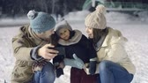 snowfall : Joyous young family of three taking some happy selfies at outdoor skating rink in falling snow