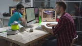 strojírenství : Two young men creating 3d models with computer software and printing them on 3D printerat small design studio