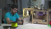 filamento : Young freelance designer in glassesusing laptop to operate 3d printing process Vídeos