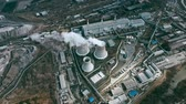 průmyslový : Aerial shot ofpower station with cooling towersproducing steam surrounded by factories in large industrial area Dostupné videozáznamy
