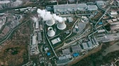 průmyslový : Aerial drone view ofpower station with cooling towersrejecting waste heat to atmosphere and producing steam surrounded by factoriesin large industrial area
