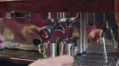 posiłek : Closeup of fresh brewed coffee dripping from espresso machine into stainless steel pitchers adjusted by barista