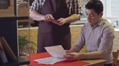 avental : Young Asian man asking waiter for advice while making order at cafe, waiter using digital tablet to take order Stock Footage
