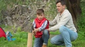 lenha : Father teaching his son how to chop wood for campfire during family camping adventure