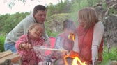 pečeně : Family consisting of father, mother, son and daughter roasting bread over campfire during summer camping vacations