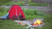 rio : Playful couple lying in camping tent and dangling their feet outside, campfire burning near picnic blanket at riverside