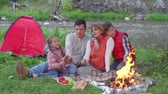 namiot : Family consisting of father, mother, son and daughter sitting on picnic blanket near campfire at riverside, kids playing with twigs and fire