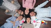 topo : Top view of young team lying on floor in circle and having fun sharing ideas Stock Footage