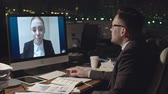 Medium shot of businessman sitting at desk and communicating with female colleague via video call on computer in dark office at night Wideo