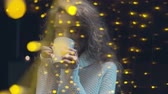 illumination : Young beautiful woman with long dark hair standing behind the window illuminated by yellow lights and drinking coffee Stock Footage