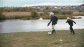 margem do rio : Two boys playing soccer on the riverbank in the countryside