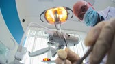 lampa : Mature dentist examining his patient teeth then starting drilling them