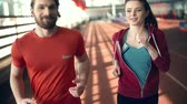estádio : Young man and woman jogging together and talking