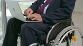 writing : Disabled businessman sitting in wheelchair and using laptop Stock Footage