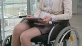 беспроводной : Businesswoman with disability sitting in wheelchair and using digital tablet