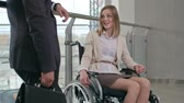chodba : Woman in wheelchair talking to businessman standing in the corridor in modern office building Dostupné videozáznamy