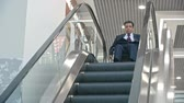 escada rolante : Disabled businessman riding wheelchair to moving escalator, looking down and then going back