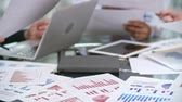 diagram : Closeup of financial documents with bar graphs and diagrams, organizer, laptop, tablet on the table and hands of business people working with papers defocused Stock Footage