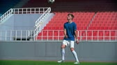 pontapé : Young soccer player training his juggling skills on empty stadium in slow motion Stock Footage