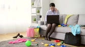 tall : professional young business woman after work back to home using mobile phone calling for colleague discussing work with many mess toys and clothing in living room.