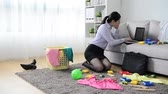 önemsiz şey : business manager using mobile cell phone calling with client when she after work sitting on living room floor sweeping messy toys with clothing.