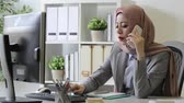 discutir : smiling attractive female muslim business woman using mobile cell phone talking with client discussing company case plan Vídeos