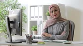 scarf : professional beauty muslim female office worker face to camera when she sitting in workplace.