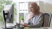 staff : attractive pretty muslim woman manager using pen writing personal schedule on notebook when she working in company office.