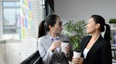 великолепный : happy charming Asian women team worker have a great conversation and take rest beside of the window of the office.