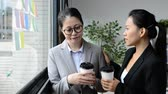 ask : Asian business woman manager tries to help her team and ask for having coffee to relieve the depression pressure.