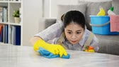 czystość : woman cleaning table carefully at home in the living room. mixed race asian chinese model.