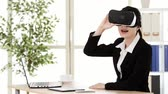 experiência : chinese asian girl office worker is surprised at 3D visual by VR device because of screen dimensional effect shocking while at the desk in modern office studio. Vídeos