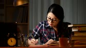 japonês : Serious asian young student studying with books and computer in dark room at home. mixed race asian chinese model.