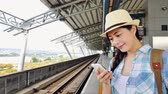ferrovia : beautiful young woman looking at the railroad for delay late train coming. Asian holiday travel concept.