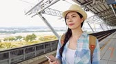 ferrovia : charming Asian woman at train station arriving at destination leaving vehicle with hand luggage. Happy beautiful girl on commute to vacation in city. Stock Footage